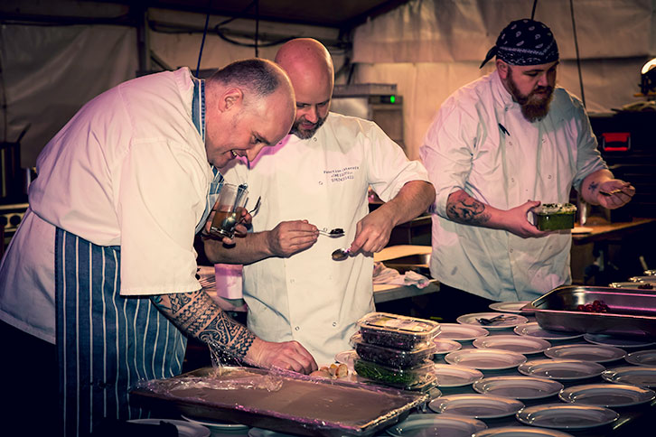 Three Function caterers chefs plating up food in an outside kitchen