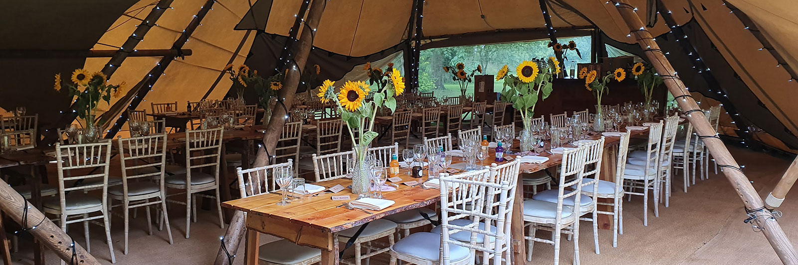 Function caterers event in a tent with tables laid out with vases of sunflowers