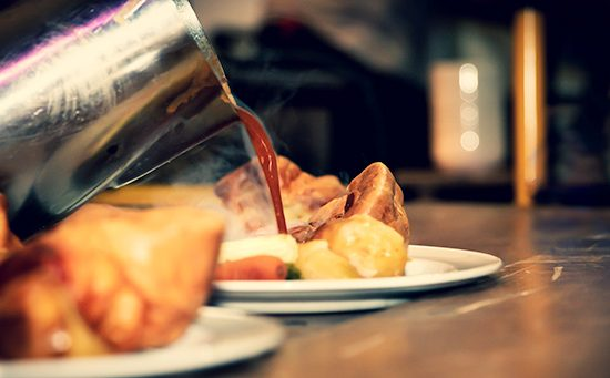 gravy being poured onto a roast dinner